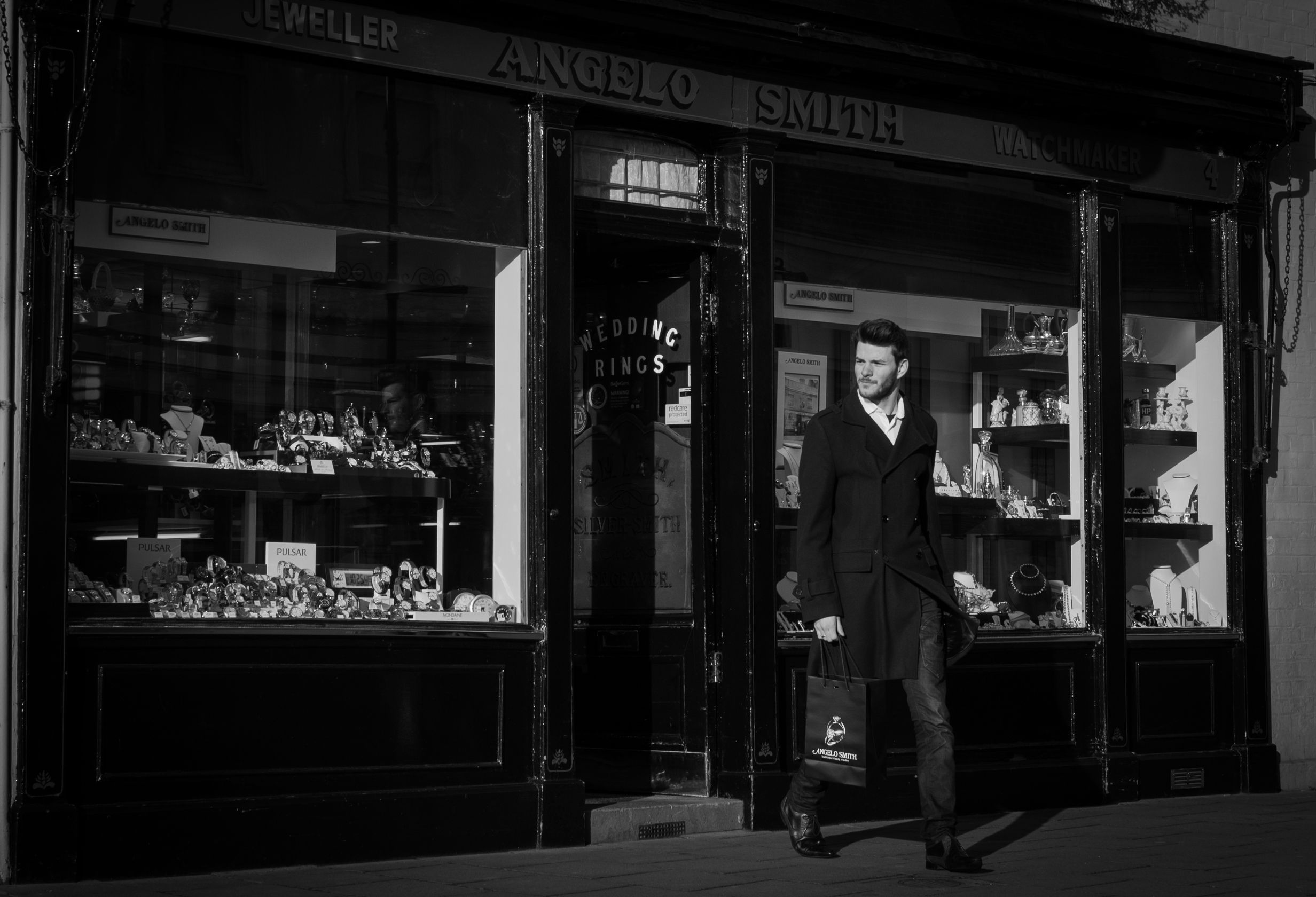 A monochrome image of a male customer leaving the showroom with an Angelo Smith branded bag in his hand.