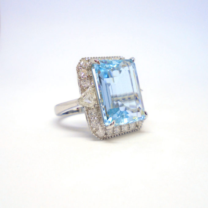 An aquamarine ring encrusted with small diamonds around the square edge