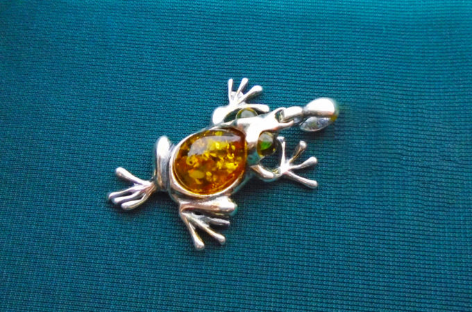 A silver frog pendant with amber in its body