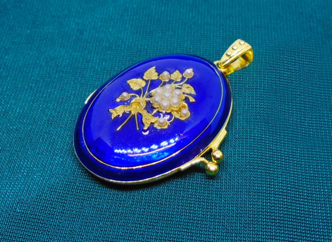 A blue enamel locket with gold coloured inlay