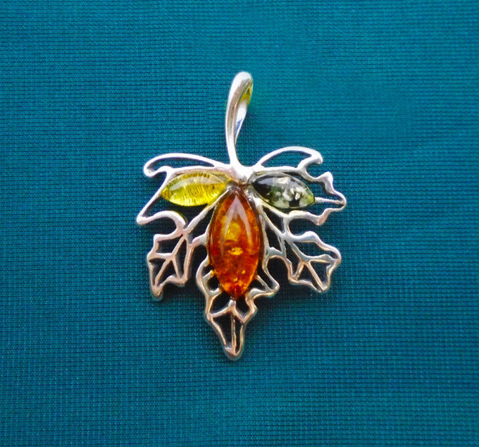 A silver leaf with 3 coloured amber stones in the middle